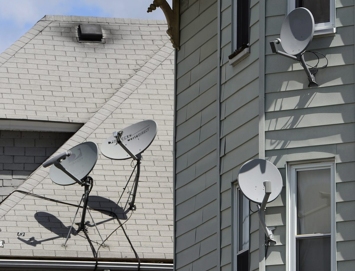 epa04214261 DirecTV receiver dishes on a home in Somerville, Massachusetts, USA 19 May 2014. Telecommunications giant AT&T has agreed a deal to take over DirecTV, a satellite dish service, for 48.5 billion dollars, the companies announced 18 May 2014. AT&T will acquire DirecTV's 38 million subscribers. The deal comes as competition is heating up among cable, satellite and telephone companies to provide television and internet service to homes, while viewers increasingly migrate to consuming television, video and other media on mobile devices.  EPA/CJ GUNTHER ORG XMIT: CJX01